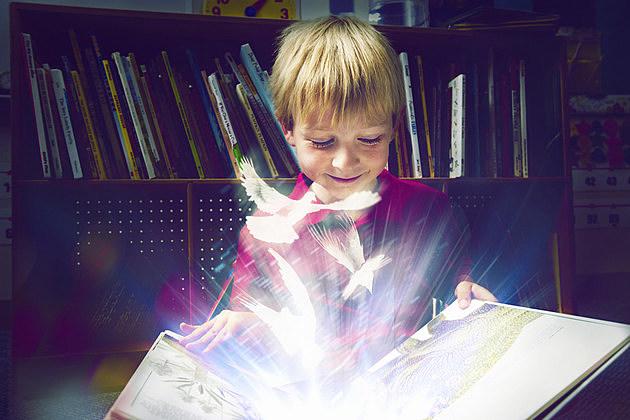 Little boy reading a magical book