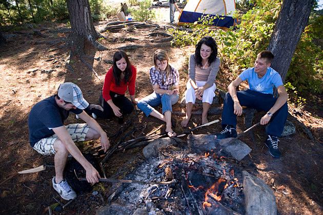Five friends sitting around campfire