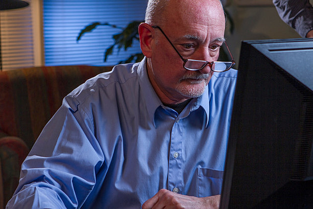 Older man using home computer, horizontal